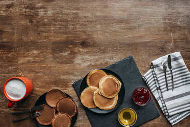 top view of freshly baked pancakes and coffee on wooden table