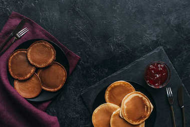 top view of various pancakes in plates on black surface
