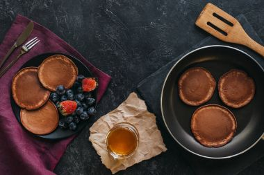 top view of tasty pancakes on plate and frying pan on black tabletop