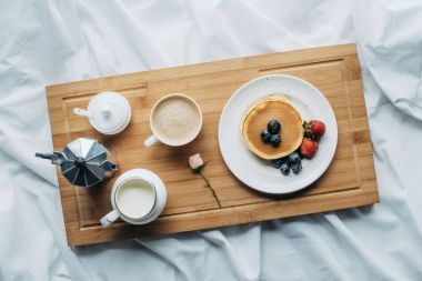 top view of breakfast in bed with freshly baked pancakes and coffee on wooden tray