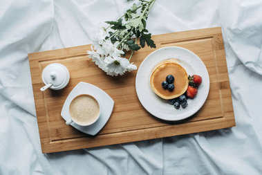 top view of breakfast in bed with delicious pancakes and coffee on wooden tray