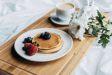 breakfast in bed with pancakes and coffee on wooden tray