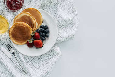 top view of plate of delicious pancakes with berries on white table