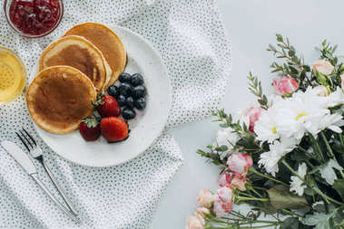 top view of tasty breakfast with pancakes and flowers bouquet on white