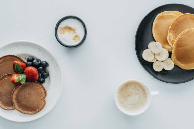 top view of delicious breakfast for two with pancakes and coffee on white table