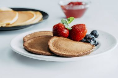 plate with delicious pancakes and berries on white table