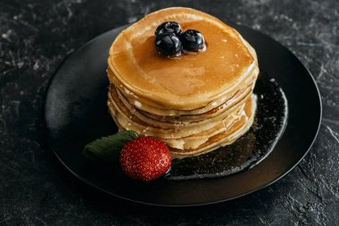 stack of freshly backed pancakes with berries on black table
