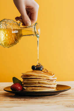 cropped shot of person pouring maple syrup onto stack of pancakes