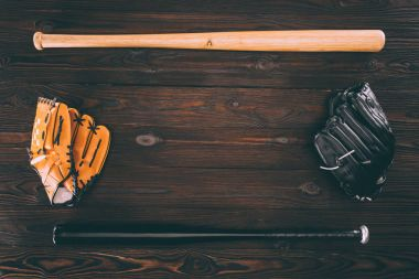 top view of leather baseball gloves and bats on wooden table