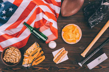 top view of junk food, american flag and sport equipment on wooden table