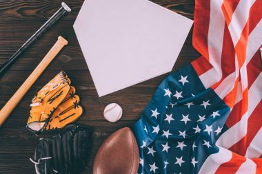 american flag and sport equipment with blank paper on wooden table
