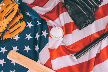 top view of baseball ball, bats and gloves on american flag