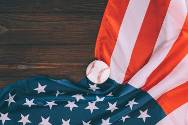 top view of baseball ball and american flag on wooden table