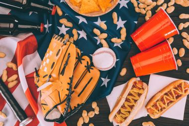 top view of hot dogs, plastic cups, peanuts, beer bottles, baseball ball and glove with bat on american flag