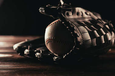 close-up view of leather baseball ball and glove on wooden table