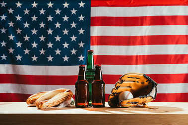 close-up view of beer bottles, hot dogs, leather glove and baseball ball on wooden table with us flag behind