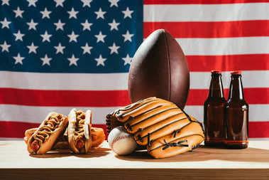Beer bottles with hot dogs and sport equipment with american flag behind stock vector