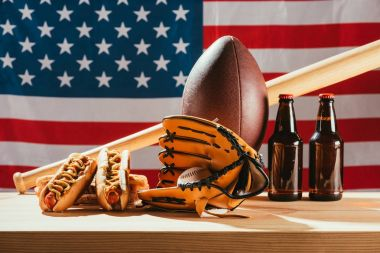 close-up view of beer with hot dogs and sport equipment with american flag behind