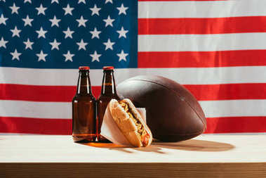 close-up view of beer bottles, hot dog and rugby ball on wooden table with us flag behind