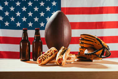 close-up view of hot dogs, beer bottles, rugby ball and baseball glove with ball on wooden table with us flag behind