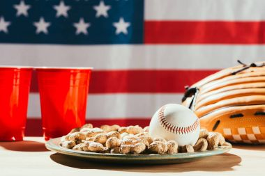 Close-up view of baseball ball on plate with peanuts, red plastic cups and baseball glove on table with us flag behind stock vector