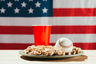 Close-up view of baseball ball on plate with peanuts, red plastic bottle and american flag behind stock vector