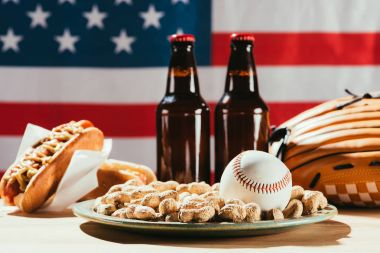 close-up view of baseball ball on plate with peanuts and beer bottles