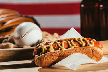 close-up view of hot dog, baseball bat and sport equipment on wooden table