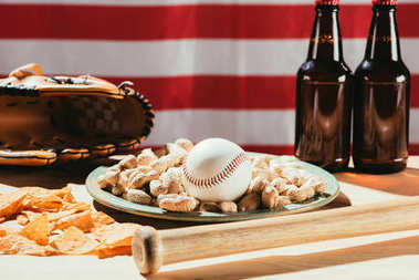 close-up view of baseball ball on plate with peanuts, bat and beer bottles, leather glove and american flag