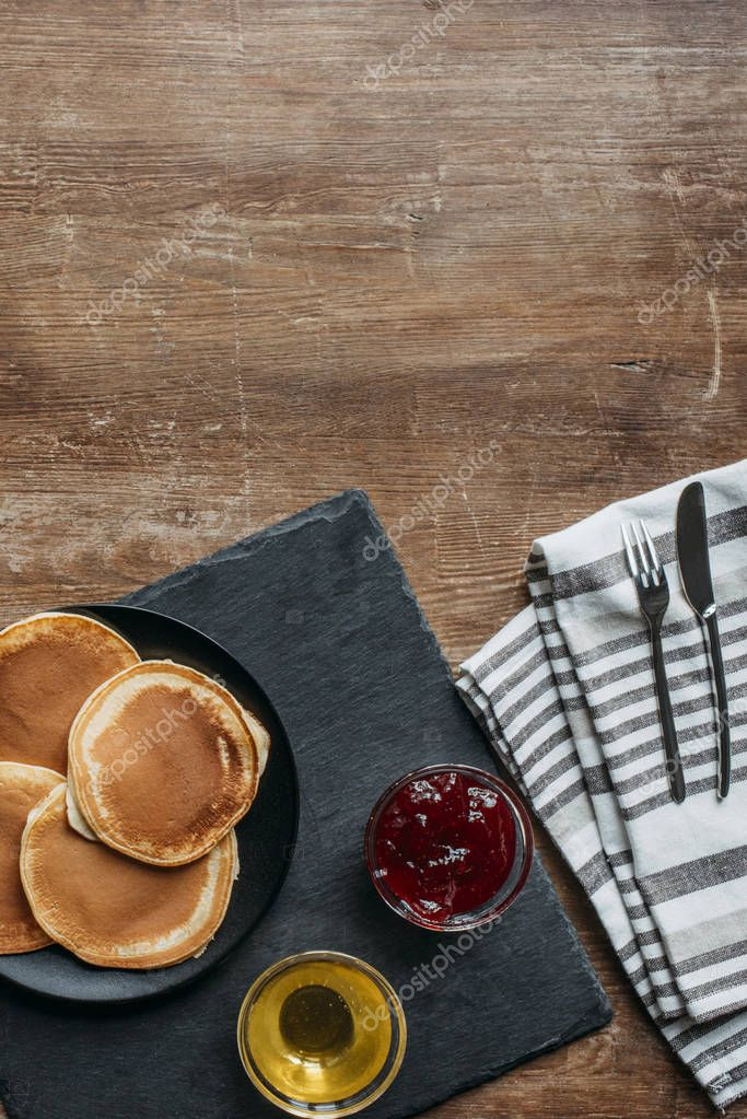 top view of tasty pancakes with maple syrup and jam on wooden table