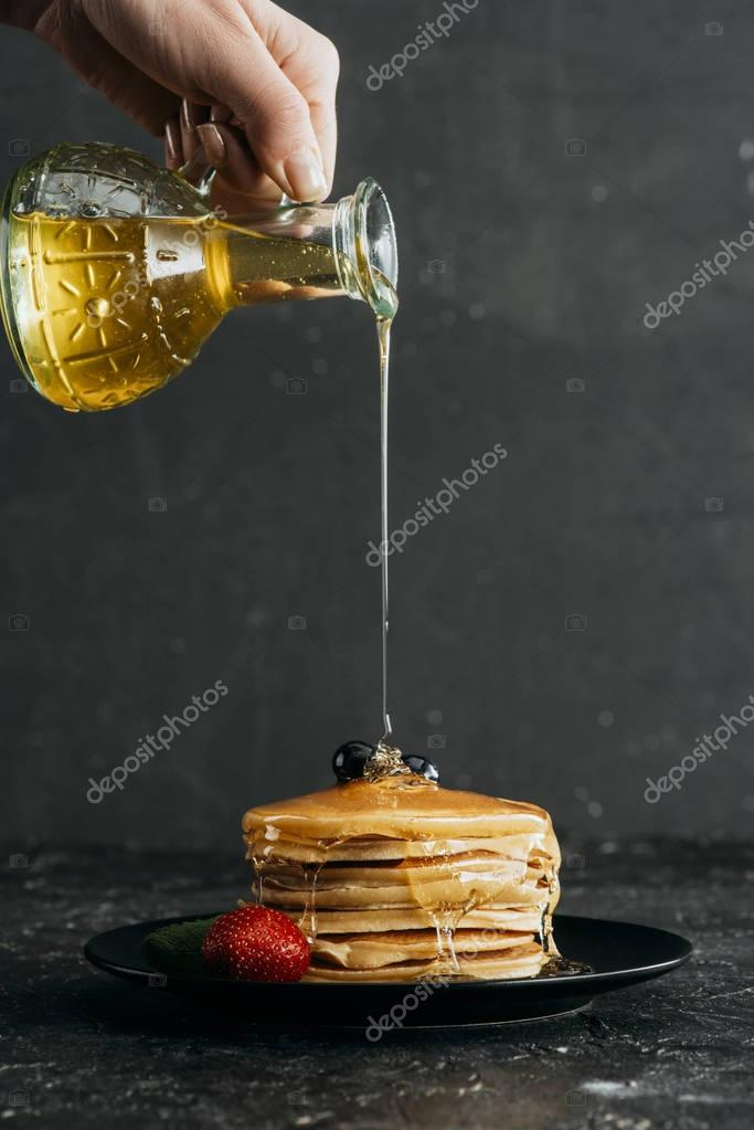 cropped shot woman pouring maple syrup stack freshly baked pancakes — stock photo © vadimvasenin