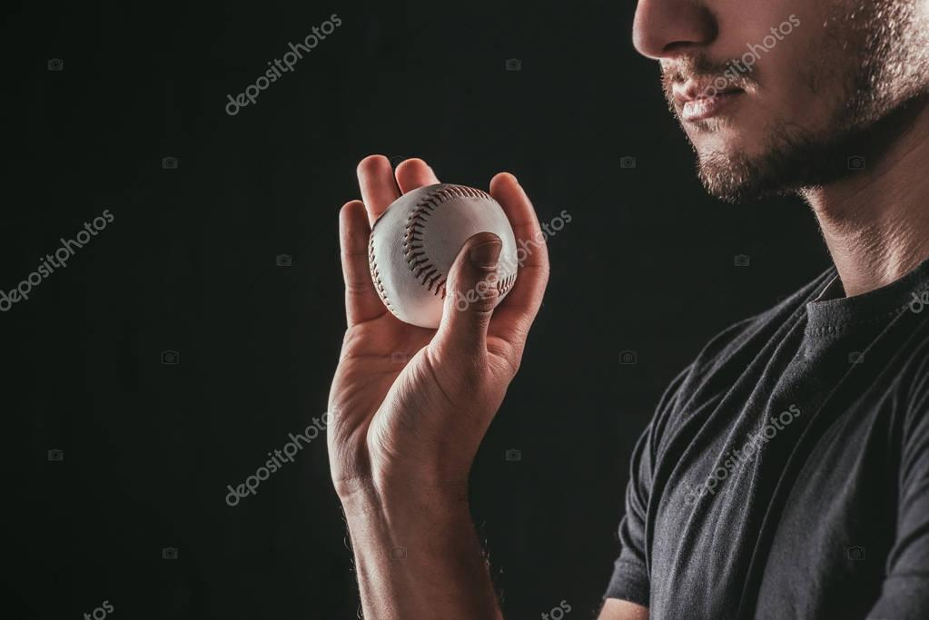 cropped shot of young bearded sportsman holding baseball ball isolated on black