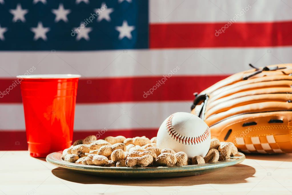 close-up view of baseball ball and glove, peanuts and red plastic cup
