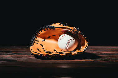 close-up view of baseball ball and glove on wooden table