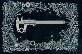 Fotografie top view of metal vernier caliper, screws and clinchers on dark tabletop