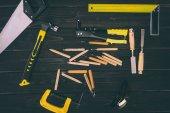 pohled shora různých truhlářských nástrojů na tmavý dřevěný povrch