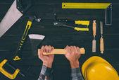 částečný pohled Carpenter drží sekeru s různými průmyslové nástroje kolem na dřevěnou desku