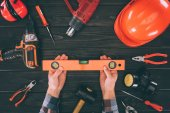 Photo cropped shot of worker holding spirit level and various supplies on wooden tabletop