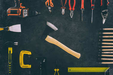 flat lay with axe and various arranged carpentry equipment on dark surface