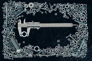Top view of metal vernier caliper, screws and clinchers on dark tabletop stock vector