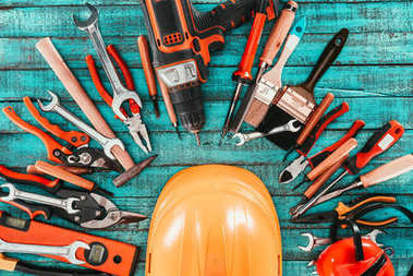 flat lay with various carpentry equipment with helmet in middle on blue wooden surface
