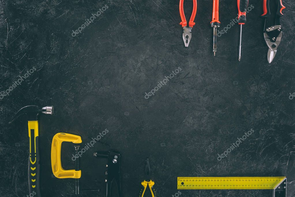 top view of various mechanical tools for work on dark tabletop