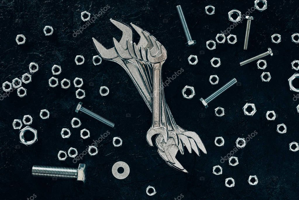 flat lay with metal wrenches, screws and clinchers on dark surface