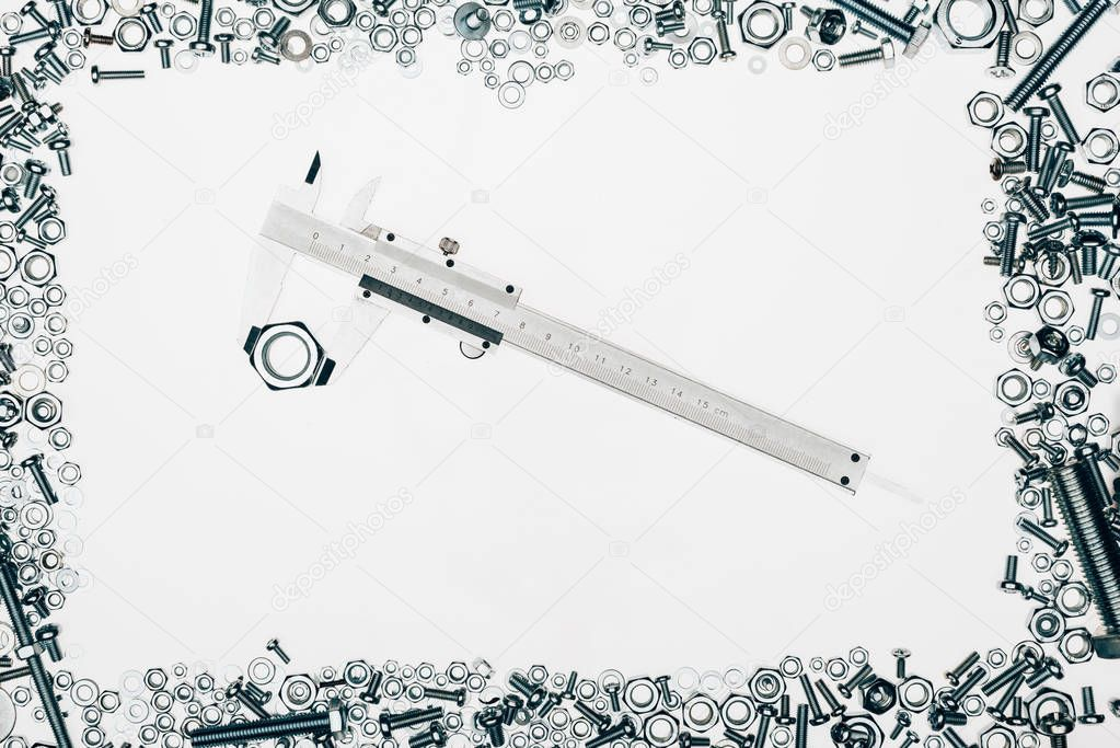 top view of arranged various metal engineering details with vernier caliper in middle isolated on white