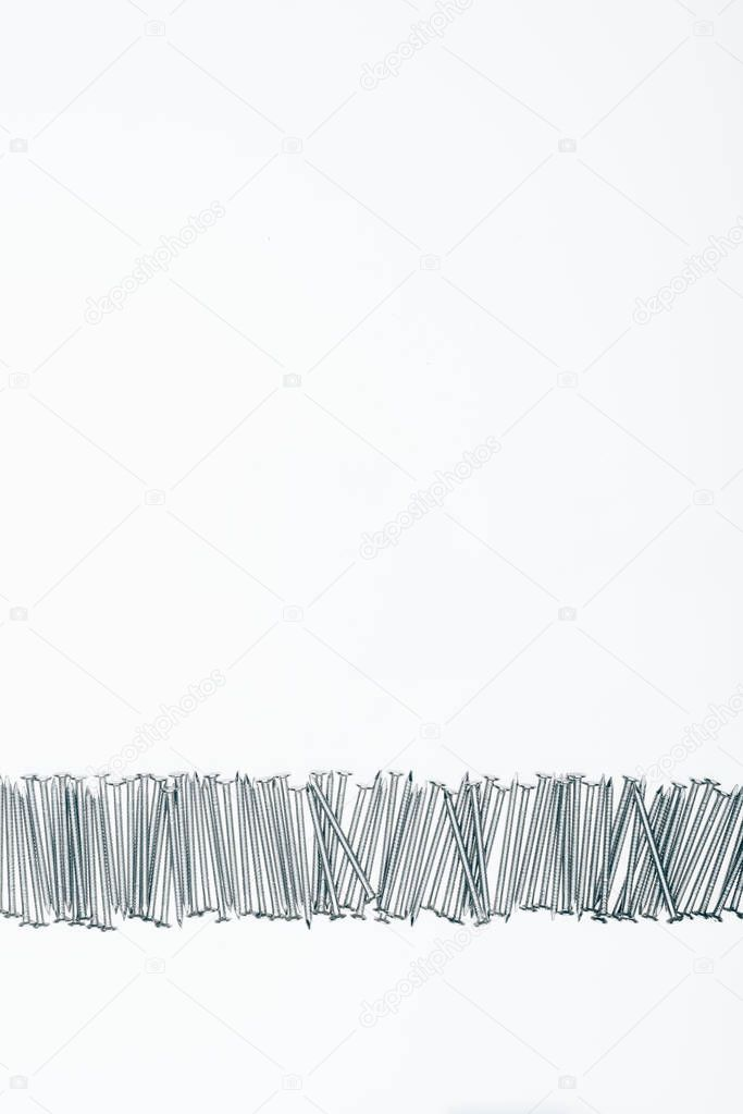 top view of arranged metal framing nails with copy space isolated on white