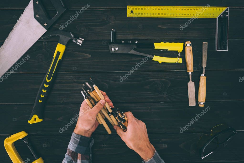 partial view of carpenter holding chisels with various industrial tools around on wooden tabletop