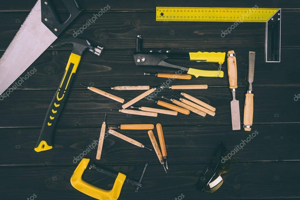 top view of various carpentry tools on dark wooden surface