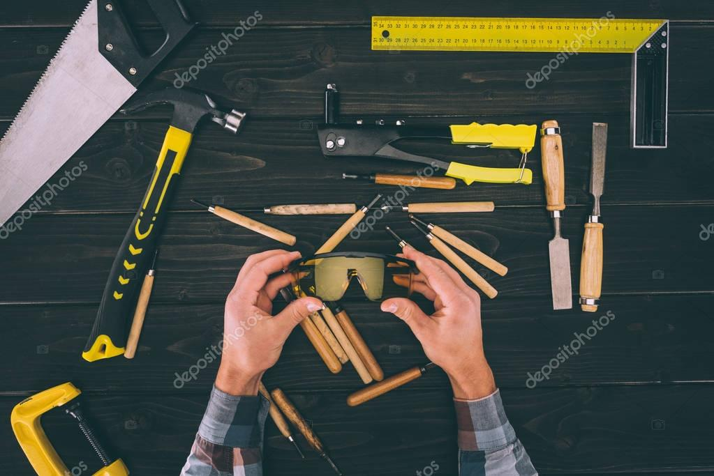 partial view of carpenter holding goggles in hands with various industrial tools around on wooden tabletop