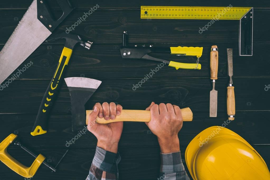 partial view of carpenter holding axe with various industrial tools around on wooden tabletop