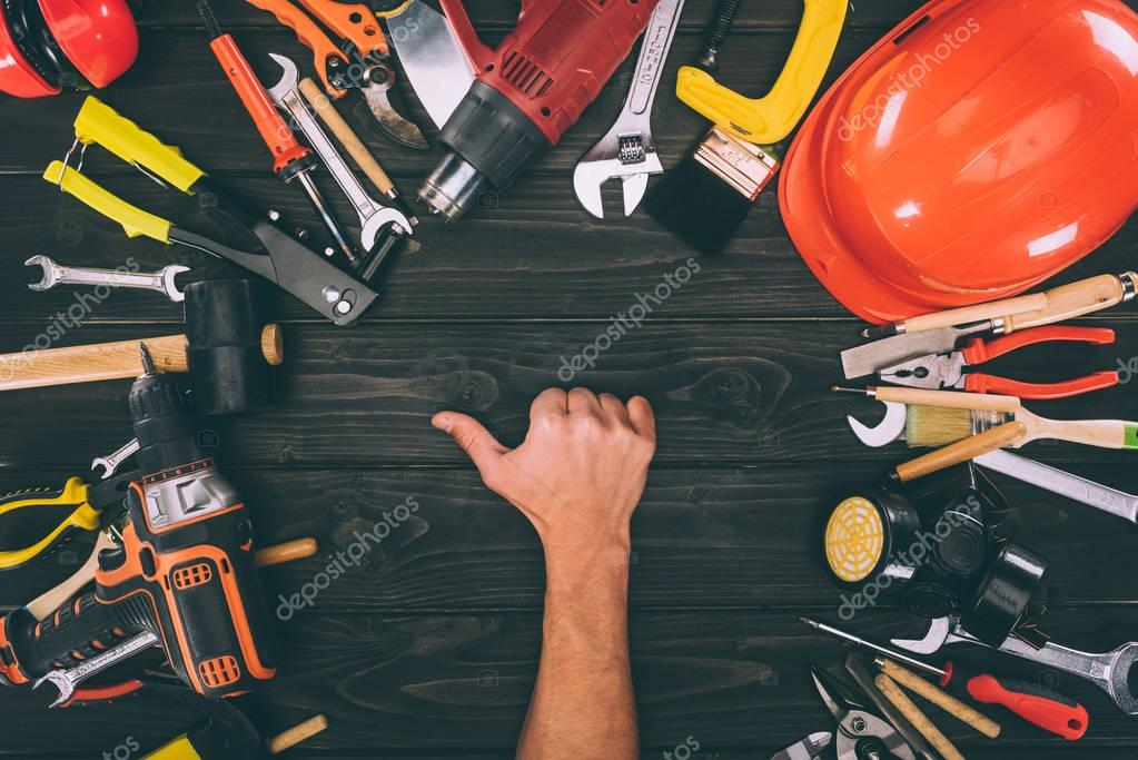 partial view of male hand showing thumb up with carpentry equipment around on wooden surface